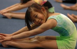 Smiling, Young Girl Stretching